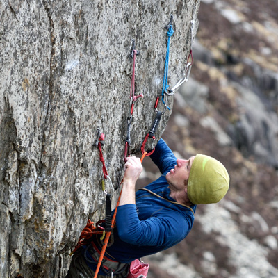 James McHaffie clipping one of the 'nest' of hooks above the overhang on the 1st ascent of House of Talons. © Ray Wood